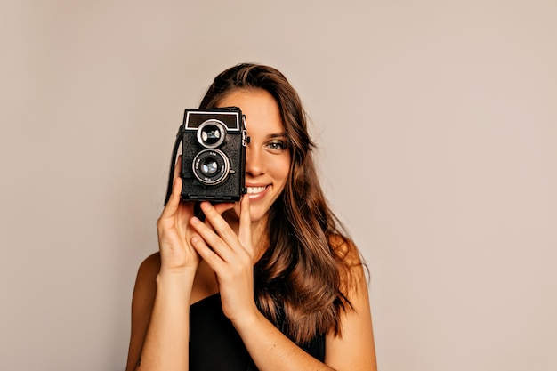 Portret van lachende mooie vrouw met lang krullend haar en lichte make-up poseren met retro camera op beige close-up