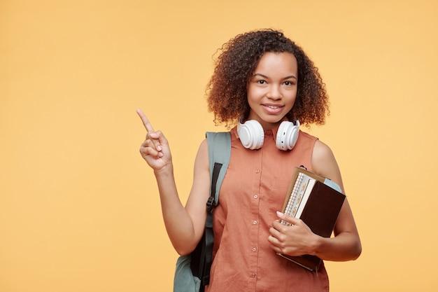 Portret van lachende mooie zwarte student meisje met afro kapsel bedrijf stapel boeken en wijzend op advertentie, gele achtergrond