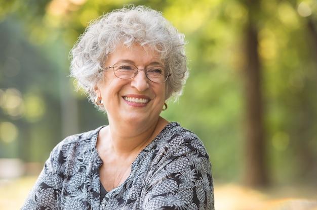 Portret van lachende oudere vrouw met bril in het park
