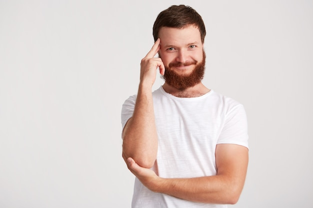 Portret van lachende peinzende knappe jongeman met baard draagt t-shirt houdt handen gevouwen, zijn slaap aanraken en denken geïsoleerd over witte muur