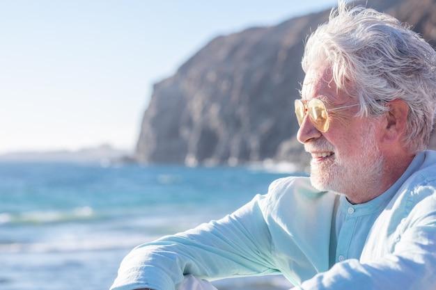 Portret van lachende peinzende senior man witharige zittend op het strand kijkend naar de horizon over zee. ouderen genieten van zomervakantie