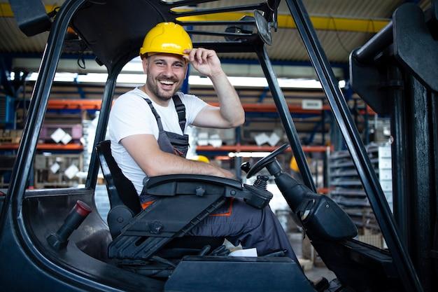 Portret van lachende professionele heftruckchauffeur in het magazijn van de fabriek