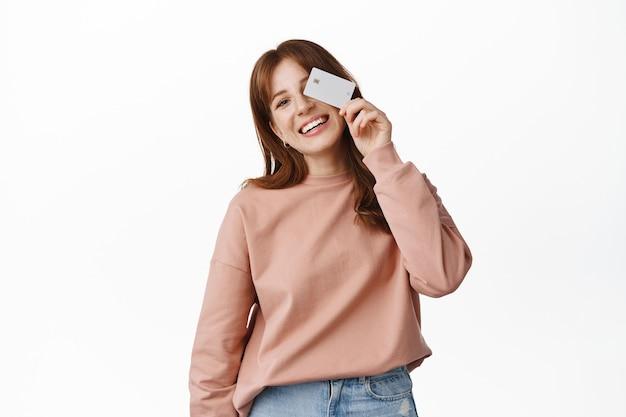 Portret van lachende roodharige vrouw con eye met creditcard, doorgaan met winkelen, contactloos betalen en er gelukkig uitzien, staande op wit