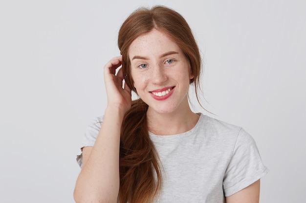 Portret van lachende schattige roodharige jonge vrouw met lang haar en sproeten ziet er tevreden uit