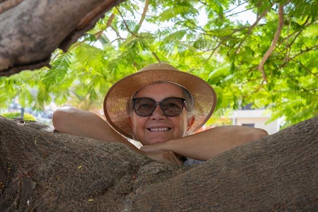 Portret van lachende senior vrouw in de schaduw van een plant in het park met armen rustend op takken - actieve gepensioneerde senioren en leuk concept