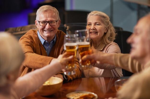 Portret van lachende senioren die bier drinken in de bar en een rammelende bril terwijl ze genieten van een avondje uit met vrienden