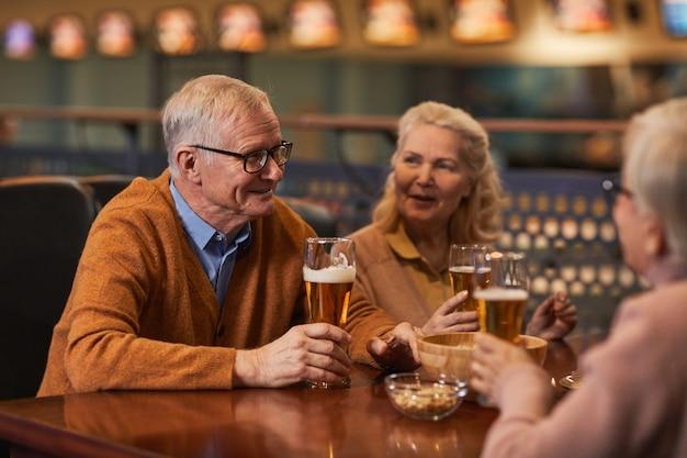 Portret van lachende senioren die bier drinken in de bar terwijl ze genieten van een avondje uit met vrienden, kopieer ruimte