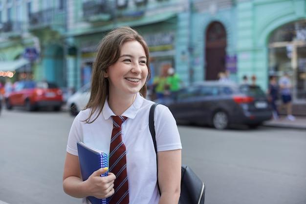 Portret van lachende studente van 17, 18 jaar oud met beugels op haar tanden, kopieer ruimte
