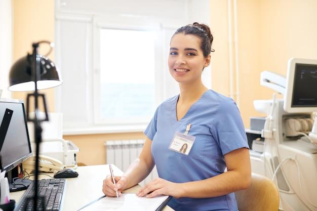 Portret van lachende succesvolle vrouwelijke chirurg met badge zit aan bureau met computer in kantoor en ondertekening document