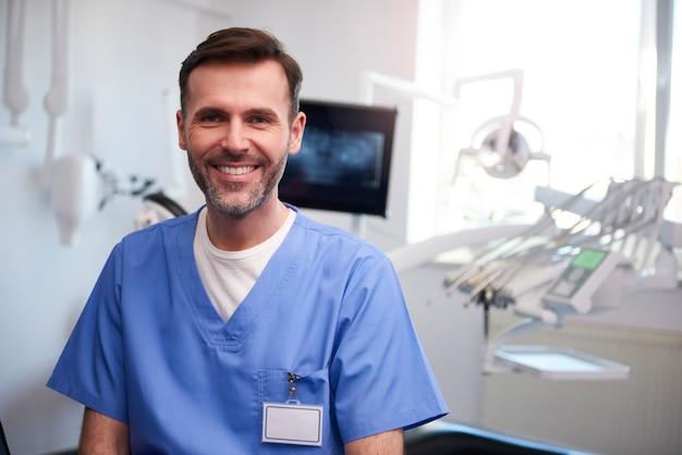 Portret van lachende tandarts in het kantoor van de tandarts