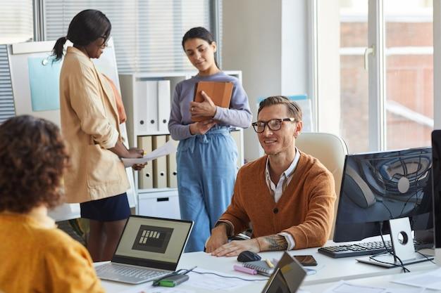 Portret van lachende teamleider die met collega's praat terwijl hij samenwerkt aan een project in een moderne it-ontwikkelingsstudio