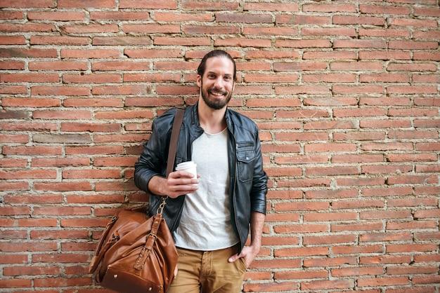 Portret van lachende tevreden europese man met vastgebonden haar op zoek naar jou terwijl je met lederen tas over bakstenen muur op straat in de stad en afhaalmaaltijden koffie drinken