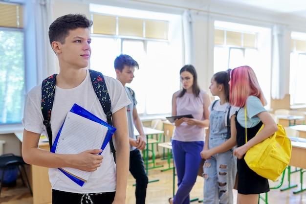 Portret van lachende tiener in de klas op pauze. achtergrondgroep pratende tienerklasgenoten en leraar. school, universiteit, studie, jeugdconcept
