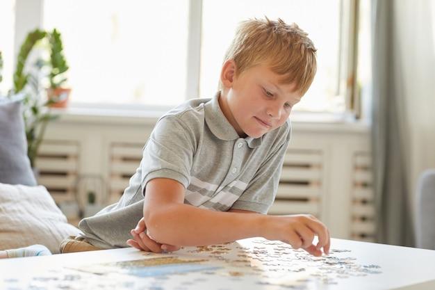 Portret van lachende tiener spelen met puzzels alleen terwijl u geniet van vrije tijd binnenshuis, kopieer ruimte
