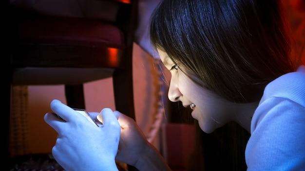 Portret van lachende tienermeisje dat 's nachts in de kamer ligt en smartphone gebruikt.