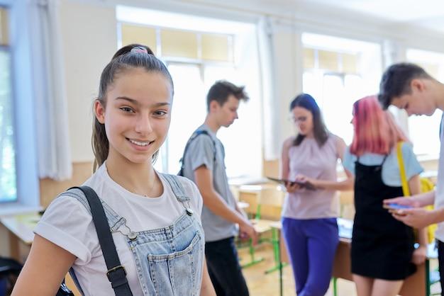 Portret van lachende tienermeisje in de klas op pauze. achtergrondgroep pratende tienerklasgenoten en leraar. school, universiteit, studie, jeugdconcept