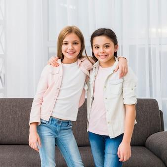 Portret van lachende twee mooie meisjes met hun armen rond de schouder