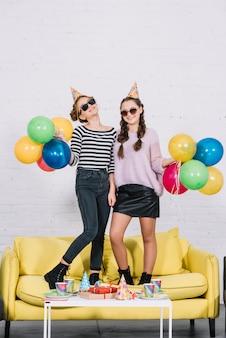 Portret van lachende twee tienermeisjes staande op gele bank kleurrijke ballonnen in de hand te houden