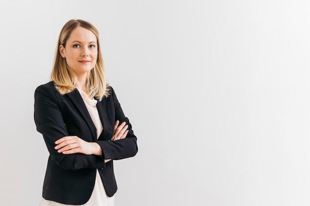 Portret van lachende vertrouwen jonge zakenvrouw met arm gekruist