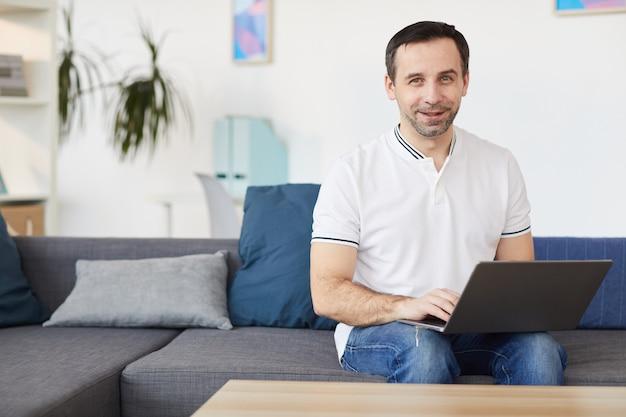 Portret van lachende volwassen man met laptop zittend op de bank thuis of op kantoor