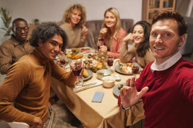 Portret van lachende volwassen man tijdens het nemen van selfie foto met vrienden en familie op thanksgiving-diner,