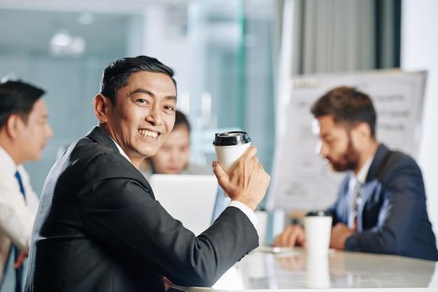 Portret van lachende volwassen zakenman met kopje koffie meenemen vergadering bijwonen van collega's