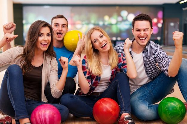 Portret van lachende vrienden op de bowlingbaan