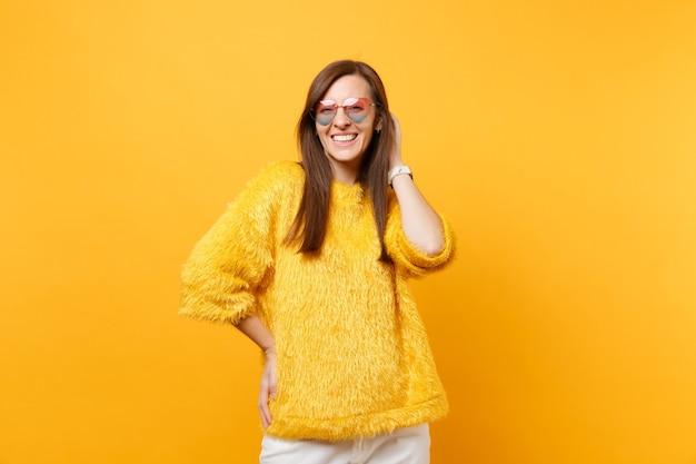Portret van lachende vrolijke jonge vrouw in bont trui, hart bril hand op hoofd geïsoleerd op fel gele achtergrond. mensen oprechte emoties, lifestyle concept. reclame gebied.