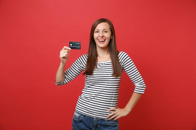 Portret van lachende vrolijke jonge vrouw in casual gestreepte kleding permanent, met creditcard geïsoleerd op felrode muur achtergrond. mensen oprechte emoties, lifestyle concept. bespotten kopie ruimte.