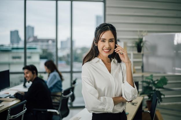 Portret van lachende vrolijke klantenondersteuning met staande headset.
