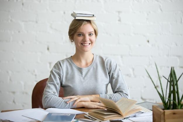 Portret van lachende vrouw bij bureau, boeken op haar hoofd