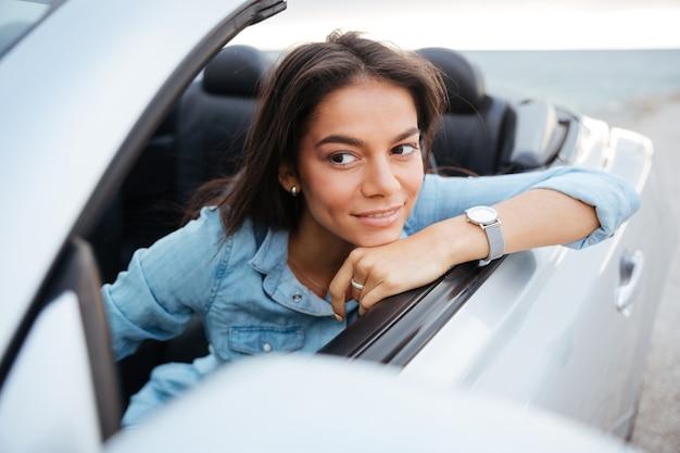Portret van lachende vrouw converteerbare auto rijden op strand