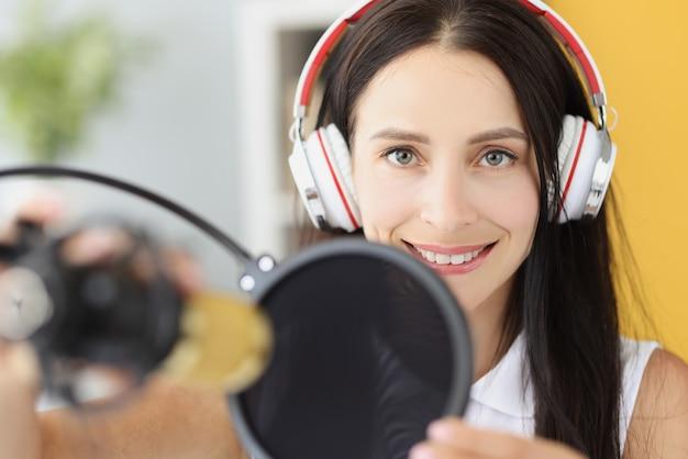 Portret van lachende vrouw in koptelefoon voor microfoon in studio