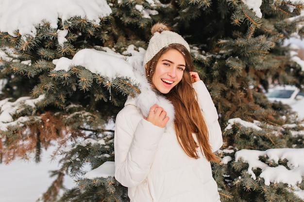 Portret van lachende vrouw in warme witte jas poseren naast boom in ijzige dag. buiten foto van romantische dame met lang haar staande voor besneeuwde sparren tijdens winter fotoshoot.