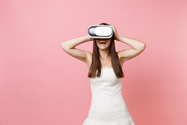 Portret van lachende vrouw in witte jurk, headset van virtual reality die zich vastklampt aan het hoofd