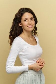 Portret van lachende vrouw in witte slijtage pose bij crème muur natuurlijke schoonheid wellness- en zorgconcept