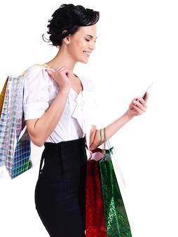 Portret van lachende vrouw met boodschappentassen en mobiele telefoon - geïsoleerd op wit.