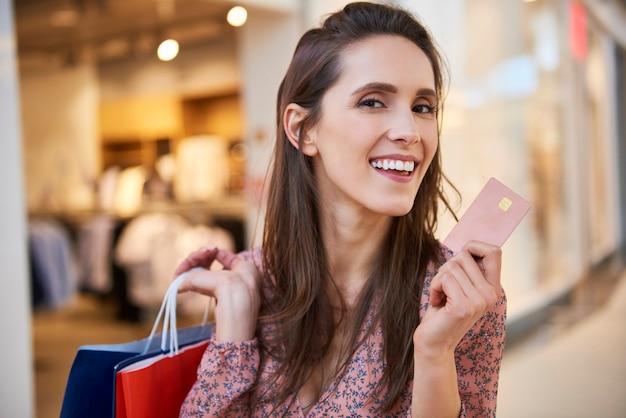 Portret van lachende vrouw met creditcard en boodschappentassen