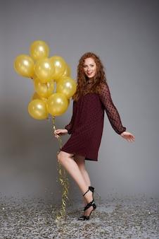 Portret van lachende vrouw met een heleboel ballonnen dansen