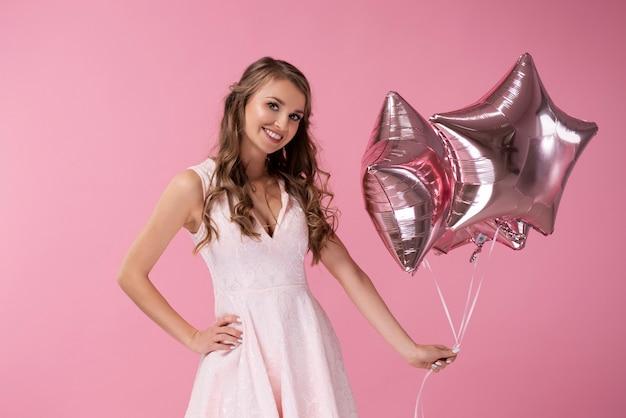 Portret van lachende vrouw met stervormige ballonnen