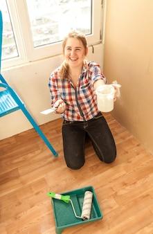 Portret van lachende vrouw met stopverf, spatel en verfroller