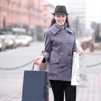 Portret van lachende vrouw met winkelen op de achtergrond wazig stad.