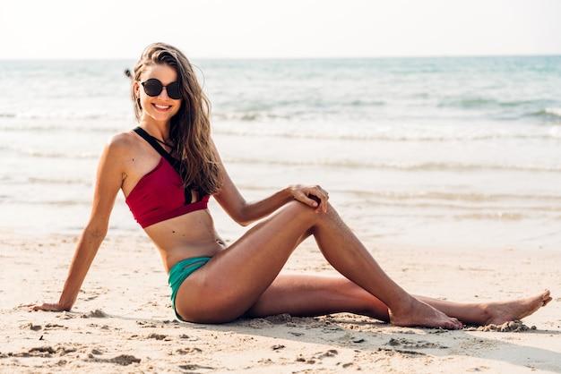 Portret van lachende vrouw ontspanning in rode bikini op het tropische strand. zomervakanties