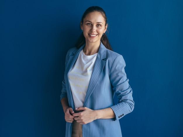 Portret van lachende vrouw poseren tegen blauwe achtergrond.