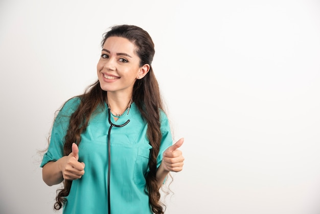 Portret van lachende vrouwelijke gezondheidswerker poseren met duim omhoog op witte muur.