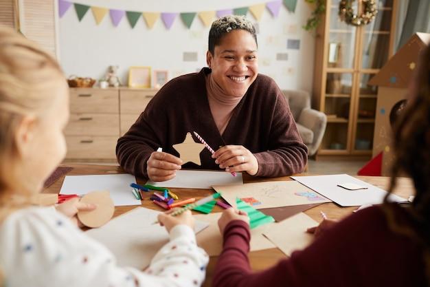 Portret van lachende vrouwelijke leraar kinderen kijken tijdens kunst en ambacht klas op school, kopieer ruimte