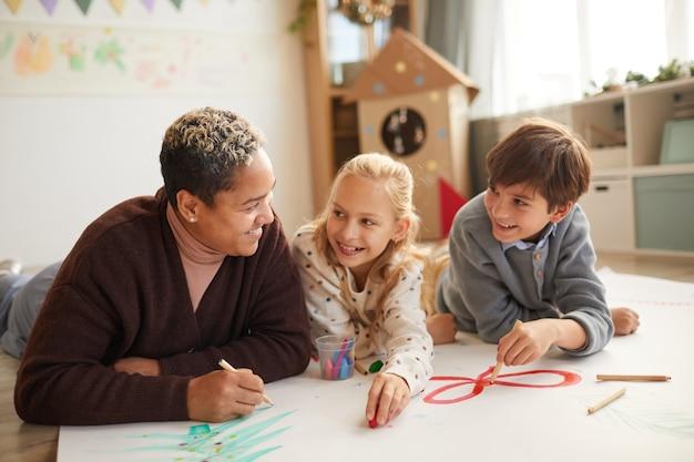Portret van lachende vrouwelijke leraar liggend op de vloer met twee kinderen tekenen van afbeeldingen terwijl u geniet van kunstles op kerstmis, kopieer ruimte