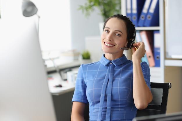 Portret van lachende vrouwelijke operator in koptelefoon op werkplek