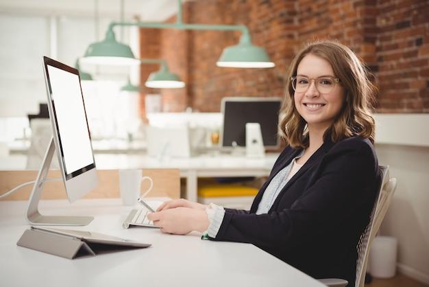 Portret van lachende vrouwelijke stafmedewerker met behulp van mobiele telefoon tijdens het werken op de computer