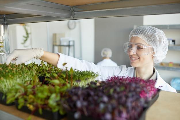 Portret van lachende vrouwelijke wetenschapper plant monsters te onderzoeken tijdens het werken in biotechnologie laboratorium, kopie ruimte